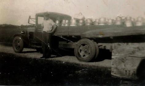 Jens Petersen med mælkejunger på ladet af bilen